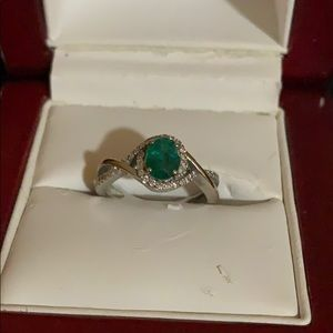 Oval ring emerald claw halo of diamonds.